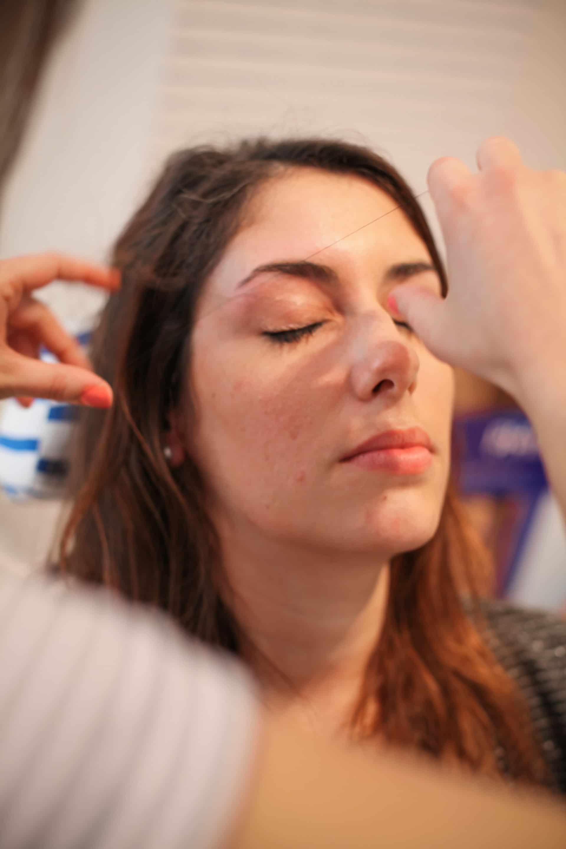 Une femme se fait épiler les sourcils au fil à la Baignoire Beauty Bar de Poitiers